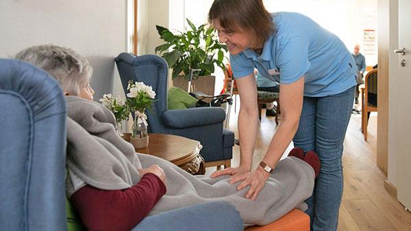 Pflegekraft im herzlichen Gespräch mit einer alten Dame.